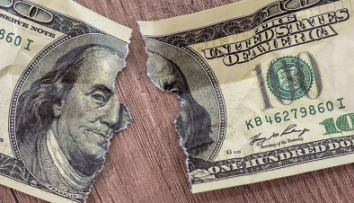 Mutilated $100 bill sits torn in half on wood table